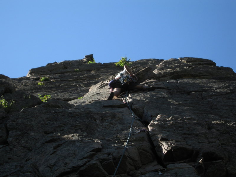 Don Owens stepping right to gain the first belay ledge ~10 feet above him. Note how well the crack takes pro on the first pitch.