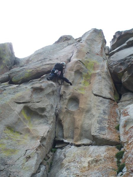 Fun steep climbing leads to a thin crack on the upper face...