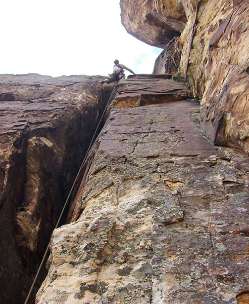 At the top of the chimney on the third pitch.  The ominous corner crack of looms above on the right.