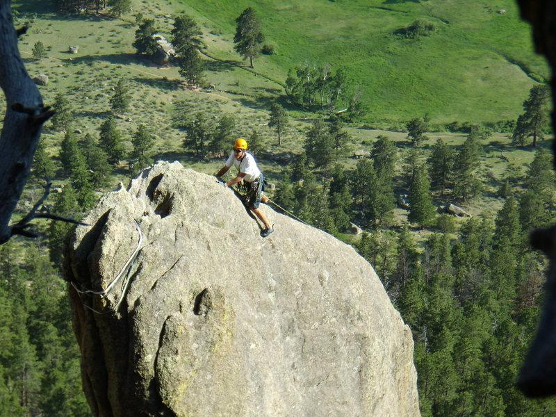 Unknown climber reaching the top of Bookmark Pinnacle. Lumpy Ridge Colorado.  June 29th 2008.
