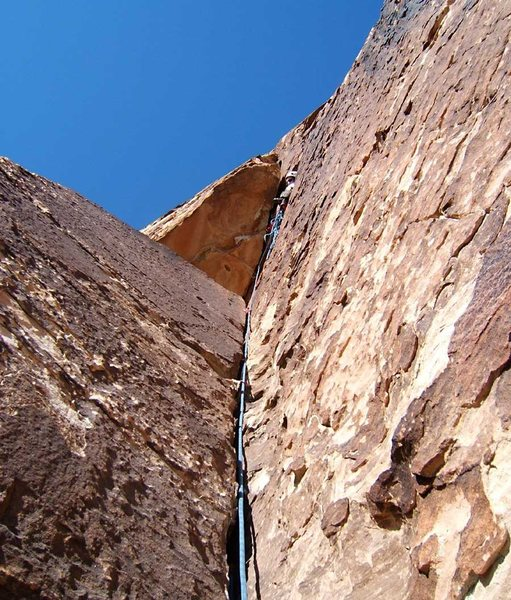 If you don't belay at the obvious bushy ledge on the second pitch, you can continue to this cramped position underneath the overhang.  You'll probably want your big cam as part of your anchor.  Your partner will appreciate that the big cam will not weigh him down on the wide crack above.