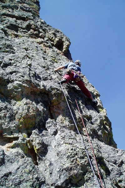Starting up the north face route. If you stay near the right edge, there's no gear for a while, but the climbing is easy on positive knobs. Be careful, though, since the rock is often hollow sounding, and I had a few holds move on me.<br> Photo by Ken Parker.