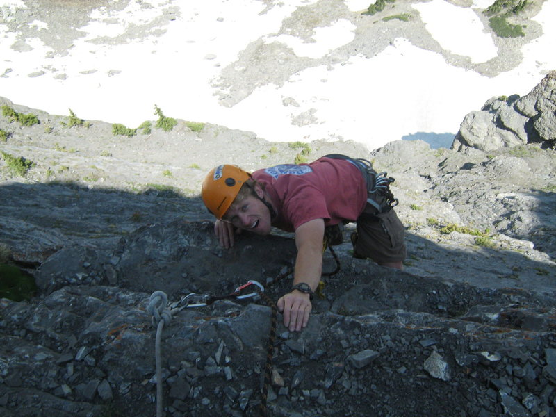 Pulling over the last bulge on pitch 5.