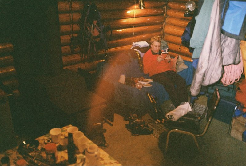 """A deeply tired Burt deeply engrossed in a dime crime novel """"McBain"""" surrounded by casted off wet ice gear at the cozy """"rustic"""" Reflection Lake cabin...."""