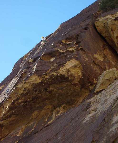 Climbing the varnished face above the overhang on Chocolate Sunday.