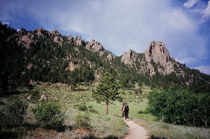 A few unknown climbers descend the trails at Lumpy Ridge in Estes Park, Colorado on a summer afternoon.