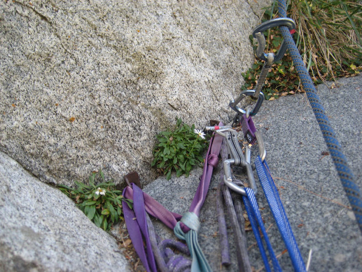 The belay at the bottom of pitch 3. The two pitons can be backed up by micro cams.