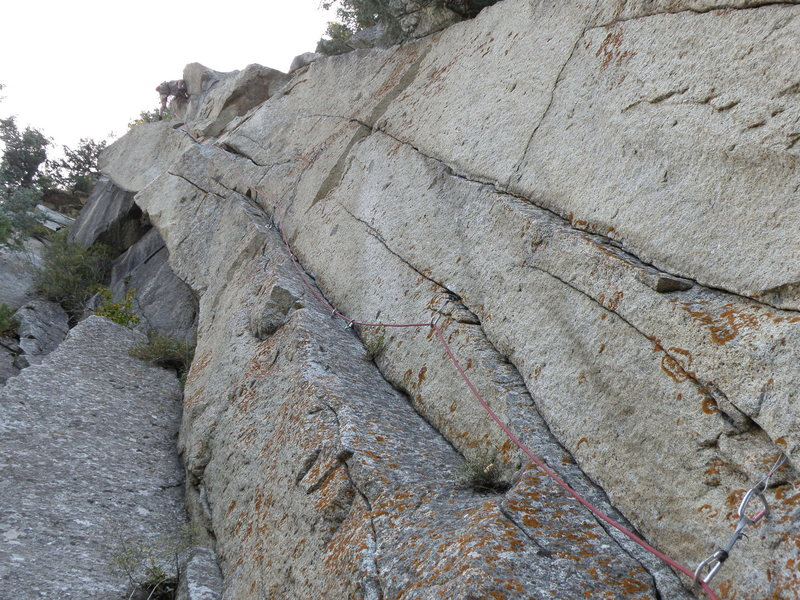 Looking up at Pudgy Gumbies from the belay. When you stand at the base in person, you can see a pin about 25' up in the left facing ramp.