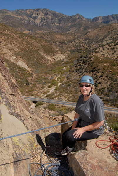 "Patty Fienup relaxes on ""Lunch Ledge,"" midway up the Central Gully of the Fortress, with Pine Mountain in the background."