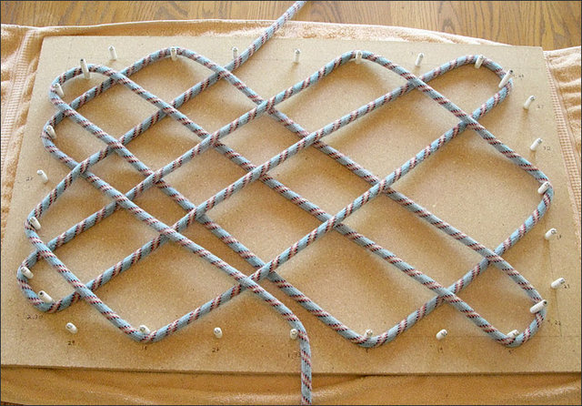 Start weaving the rope around the appropriate pegs, referring to template drawing to know when to go over or under.