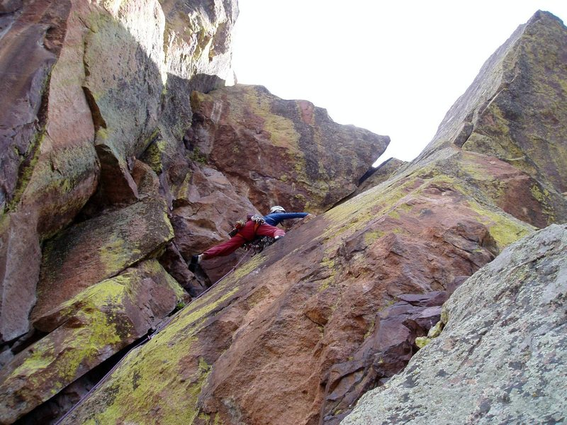 Ivan moving right below the red roof on P3. It looks possible to move left instead and up the sunny corner at the top center of the photo. P3, although intimidating, is only about 5.7.<br> Photo by Luke Clarke.