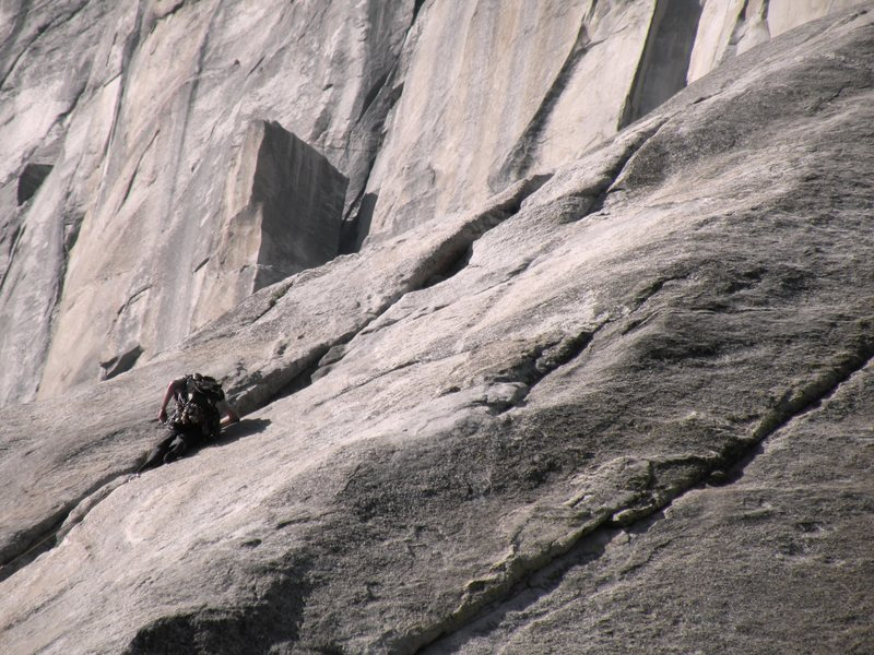 Climber on the first pitch of the Nose while El cap spire looms in the distance