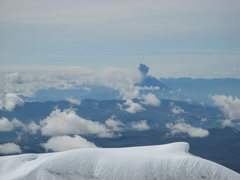 Tungurahua volcano erupting in the distance as seen form the summit of Volcan Cotopaxi. Jan, 11, 2008