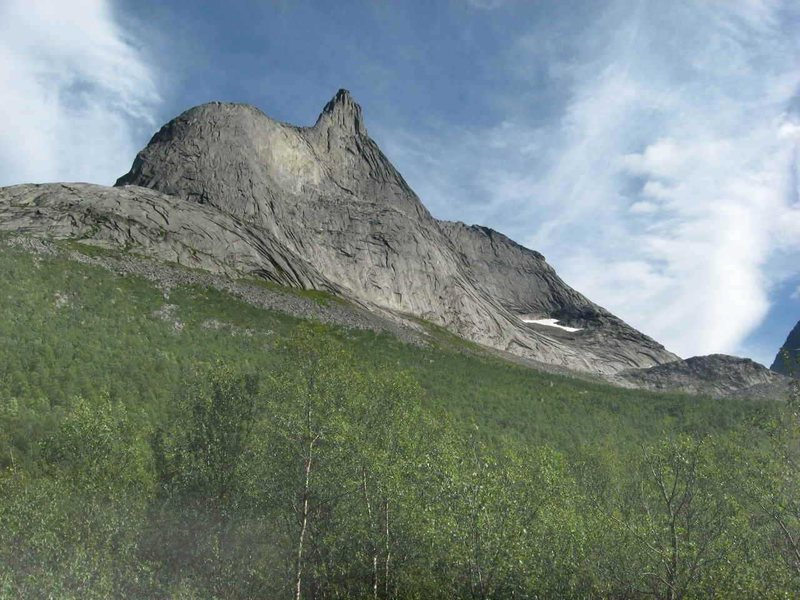 Stetinden, seen from the approach trail. The Regular Route ascends the ridge on the right side of the photo; the South Pillar is profiled against the sky on the right side of the central summit spire, sweeping down near the center of the mountain's base.