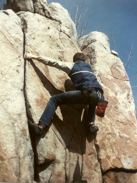 Left Crack (we called it Butterfly Jam, 5.10), was done by 1984, as was Right Crack (that one might have been 1983).  In this 1985 photo, I'm doing what we called Hercules Unchained, where both cracks are climbed to a top out on the right (we may have also toped it out on the left; can't recall).  REI harness, Asolo rock shoes, and homemade chalk bag.