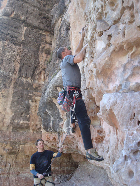 First ascent of Bluto Tastes An Olive. Erik Wolfe climbing