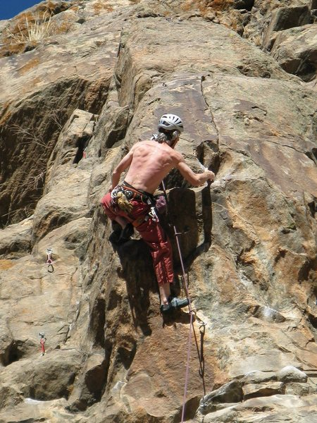 Pulling left around the arête is the first hard move.<br> Photo by Ken Parker.
