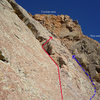 "Pay attention here! We opted for the route in red after the ""3rd class"" ramp at pitch 7 1/2, but should have traversed left towards the arete (blue line), where the arch was. The red arrow indicates where the double bolt belay station is. The last pitch, with a few bolts and fun 5.8-5.9 mantles/smears beckon."
