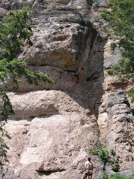 Dan Miller stares up at the cruxy part of La Babareena .11b at the Valhalla cliff in Tensleep