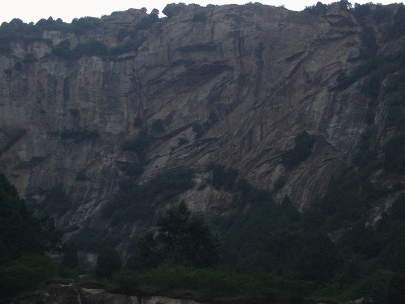 A completely unclimbed wall 100m down the road from Lao Yan Chang, just waiting for your FA. The wall looks to be 300ft+.