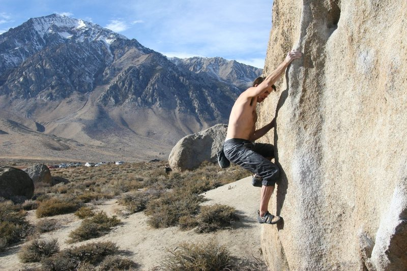 Pulling hard on the blunt arete of Problem A.