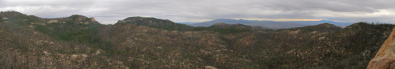 "Panorama from the belay ledge at the top of ""Thoughts of Strassman and Cochise"" on the Tall Wall at the Outcroppings. Other visible climbing areas include Ridgeline (or the parking area anyway), Barnum Rock, Lizard Rock, Middle Earth, The Helmet, and Munchkinland."