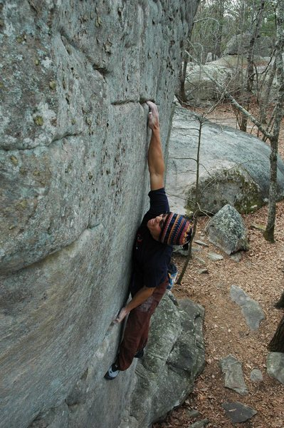 The long reach that starts the crux as this move quickly leaves onr without feet.