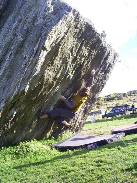 Climber at the NBS on the F-word problem. Dark Places starts at the left hand arete, traverses into this problem then out and up the right hand arete