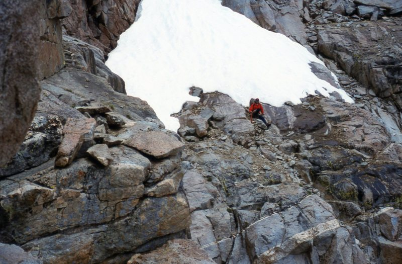 A view on the left of the irregular and sloping ledge, referred to as the Catwalk, which unlocked the key for the first ascent of North Palisade. D. Selby is sitting below the snowfield on the edge of the Southwest Chute leading up to the U-Notch.  Photo taken 21 Aug 95.