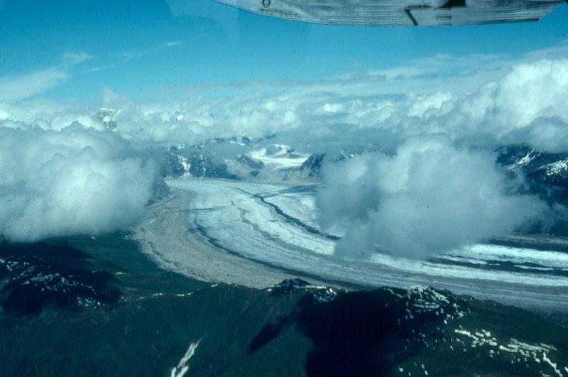 Alaska glacier, flying into Denali basecamp from Talkeetna. Colored ribbons of rock on the glacier indicate merging of several glaciers upstream.