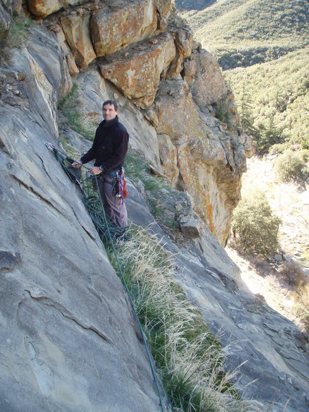Belaying from a narrow ledge, the &quot;Elephant Walk&quot;, that runs atop all existing routes at Derrydale Cliff. This grassy ledge is a comfortable place from which the leader can belay the second, and it has an outstanding view of Sespe Creek. <br> Photo by Matthew Fienup, February 2009.
