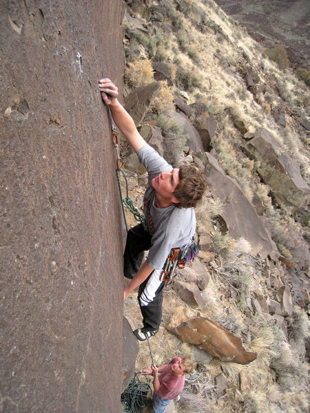 Solid body tension from the undercling allows you to move your feet up to reach some fingertip holds on the slab. February 2009.