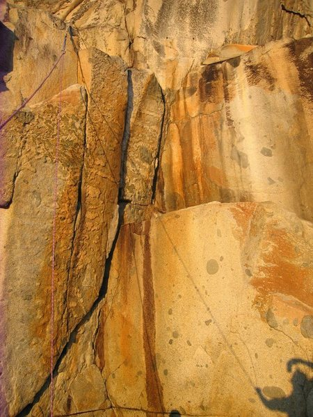 Climbs from the bottom left of photograph onto the ledge then switches to the right most crack in the center of the photo.