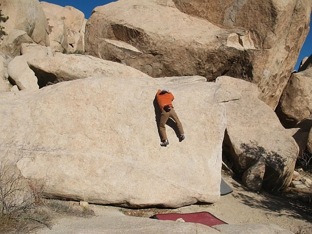 Past the crux and ready to mantle over on Lip-Synch (V1), Joshua Tree NP