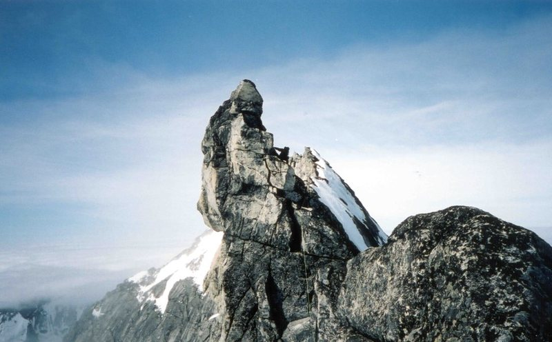 "Traversing around the 'wave-shaped' fin, just above the ""Rappel Notch"".  The summit of the Thumb is visible in the background just right of the climber's pack."