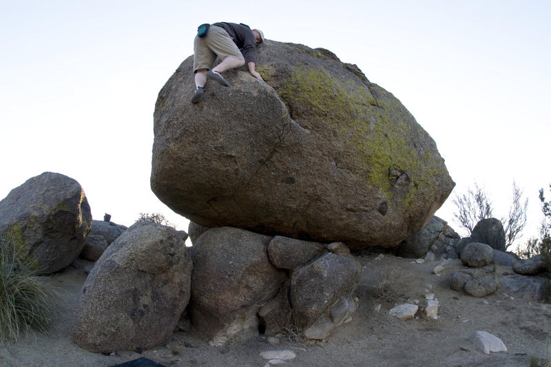 Highball on the east side of the balancing boulder (V1). Landing is flat, but pad starts to look small as you find your feet for the topout.