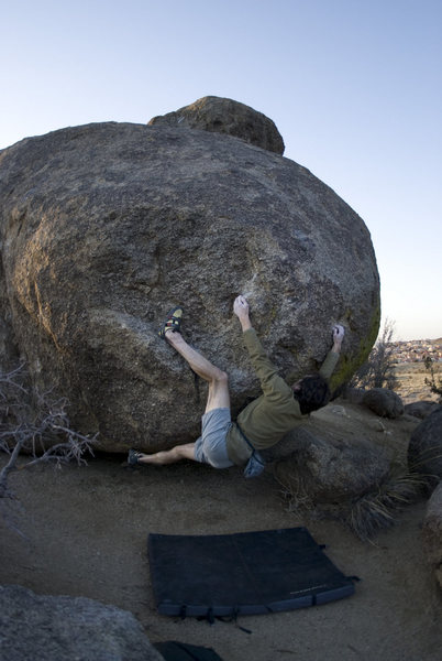 This is the low, bulgy problem at the east end of the big boulder's south face (V3). Start with both hands matched on the low shelf, and throw the left heel up to match (heel is still on start hold in the photo). Cross over with left hand to a sidepull, then swing the right hand out to a small crimp (sequence pictured here). Scrunchy to get set up to grab the upper crimps, which take you up the slopey topout.