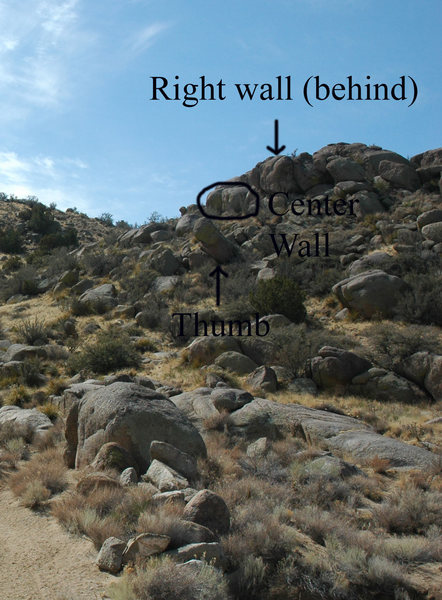 The walls that are up to the right of the boulders. There is a left wall that is not visible in the photo and the right wall is up and behind to the right of the center wall.