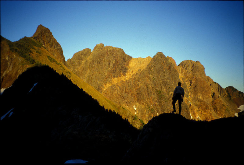 Don Serl silhouetted in front of the Settler. The traverse from south to north climbs the skyline from right to left to the second-from-left summit then descends gullies below that summit. The apparent highest summit at far left is actually a gendarme on the NW ridge.
