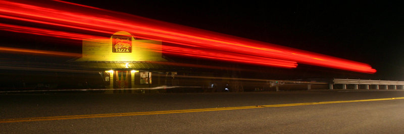 Miguels at night with brake lights zooming past...