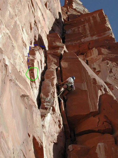 Blue line is the original Kor-Ingalls second pitch.  There is one bolt on the left wall of the crack.  Going this way means you get to use the cool hueco, circled in green. Pro your second for the traverse back right.