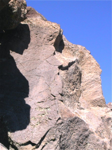 A picture of the rattlesnake boulder.  The rattlesnake arete follows the arete on the left and the smooth face. While dihedral full of rattlers mantles the small overhang and finishes in the dihedral.