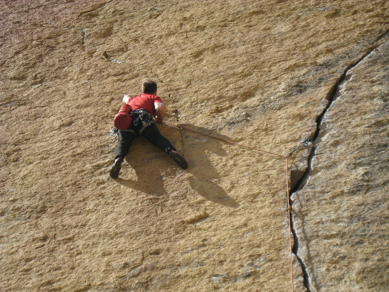 Working up the face along the thin seam, just after clipping the route's lone bolt.