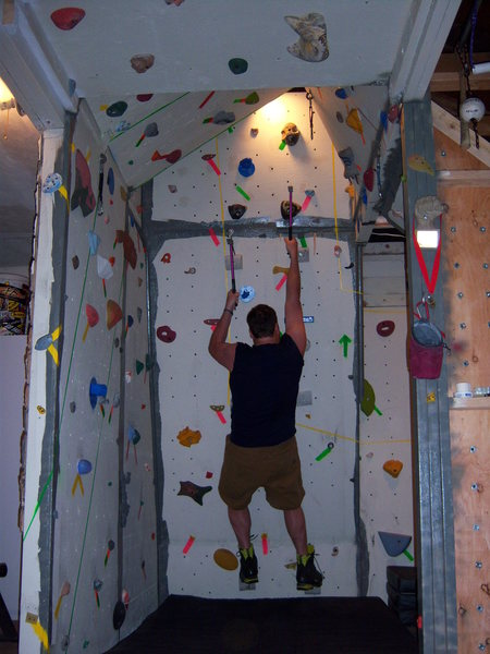 Dry Tooling my way up the overhanging side of my wall.