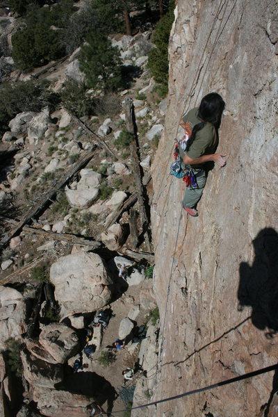 Albert Ramirez clipping bolt @POUND@4 with Agina far below on belay.