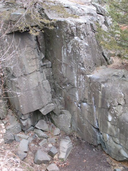 The Pit. The steep face in profile contains the problems The Crack (the crack on the right face, not the dihedral/gully), Twinkletoes (chalked line right of the Crack), One Slim Fish (left of the crack), and Shrimp Tempura. Spread Eagle starts at the prow far at right, just off frame, and moves around and left.