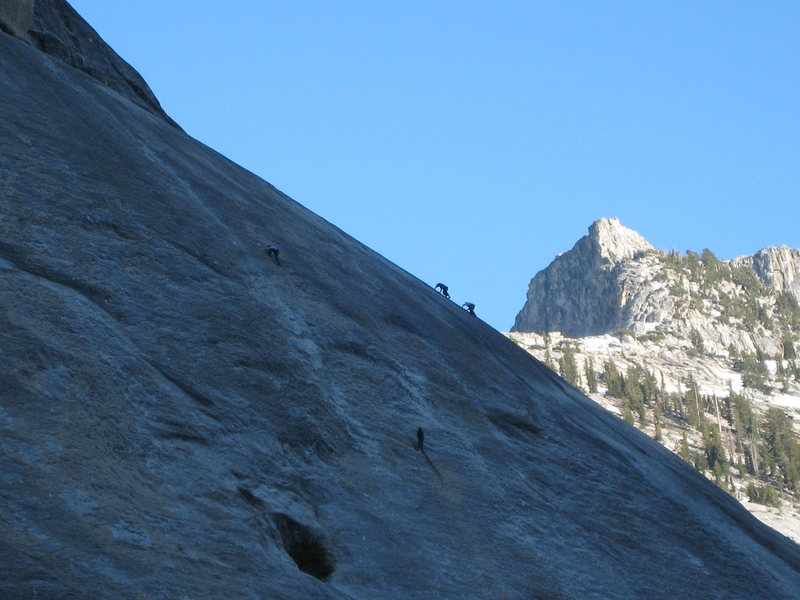 A team works on The Dike Route at the end of the day, while two free soloers are silhouetted on a line to their right.<br> <br> June 2009