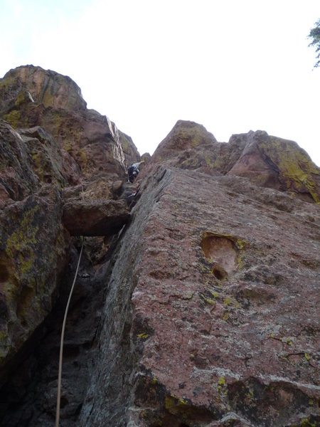 Just above the crux on the first pitch.  The chockstone identifies the route.<br> Photo: Roth.