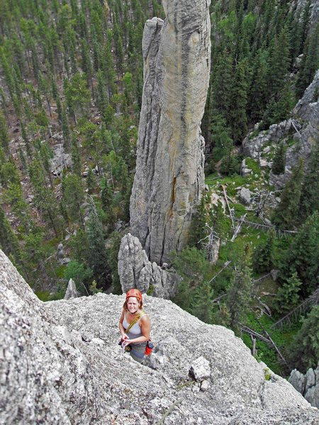 """Looking down from the summit block to Brenda standing at the bolts at the top of pitch 3.  The narrow spire in the background is """"Station 13."""""""