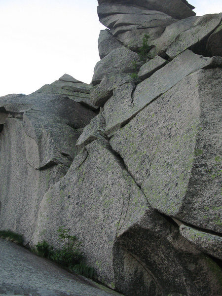 Looking up at the final pitch.  The flake that leads to the corner is visible as the whitish streak leading up and slightly right from the slab, to the left of the obvious left-leaning crack.